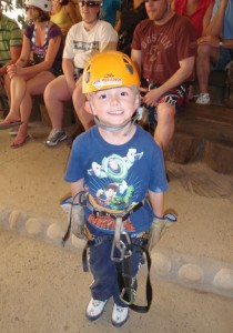Sweet little Dylan in harness smiling before zip lining.
